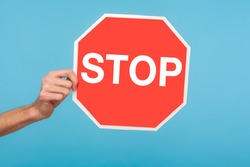 Closeup of male hand holding Stop symbol, showing red traffic sign, warning about problems, concept of ban, denial, prohibited to go, forbidden way. indoor studio shot isolated on blue background
