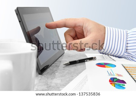 Closeup of Male Hand Touching Tablet-PC Screen with Financial Chart