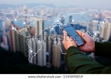 Closeup of male hands holding modern smartphone against cityscape skyscrapers  view. Infographics world map with connection network. Communication with internet everywhere.  Mobile phone for chatting