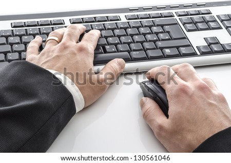 Closeup of male hands typing on keyboard on a white table.