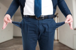 Closeup of male realtor showing his empty suit pockets as bankruptcy concept