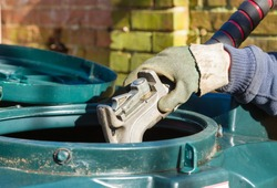 Closeup of man filling a bunded oil tank with domestic heating oil (kerosene) at a house in rural England, UK