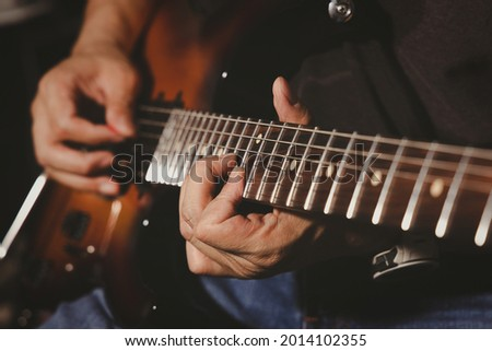 Closeup of man guitarist's fingers during press the string on the guitar neck fingerboard for chord while playing electric guitar solo. Song and music band practice. Foto stock ©
