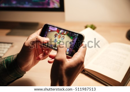 Closeup of man hands playing videogames on cell phone in the evening