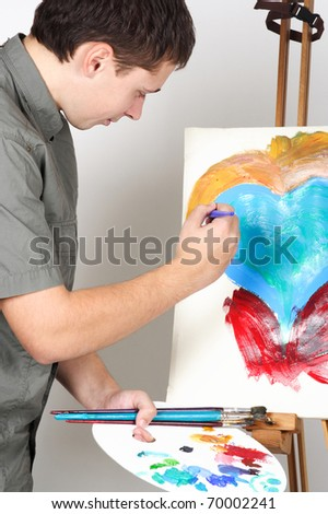 closeup of man holding brushes and palette, painting abstract picture with heart