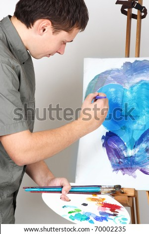 closeup of man holding brushes and palette, painting blue abstract picture