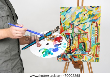 closeup of man holding brushes and palette, painting picture with abstract city