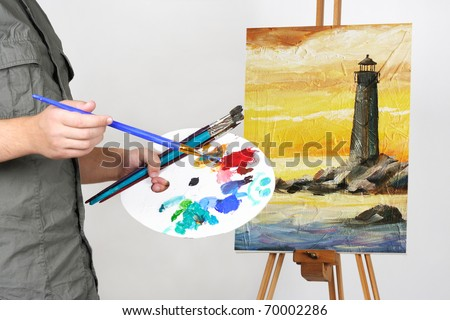 closeup of man holding brushes and palette, painting picture with sea landscape
