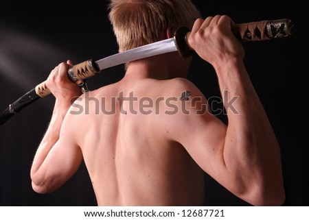 Closeup of man holding samurai sword in dramatic studio light