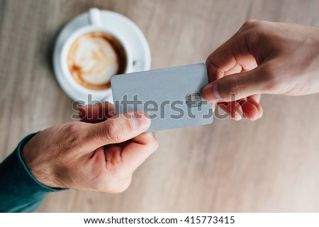 Closeup of man in cafe giving credit card to waiter #415773415
