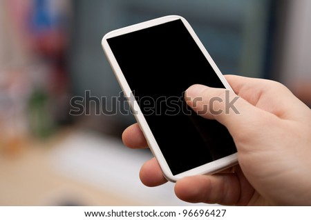 Closeup of Man's Hand Touching Screen of Smartphone in Office