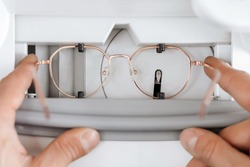 Closeup of man's hands making individual eyeglasses frame in optician workshop. Health care, medicine and vision concept