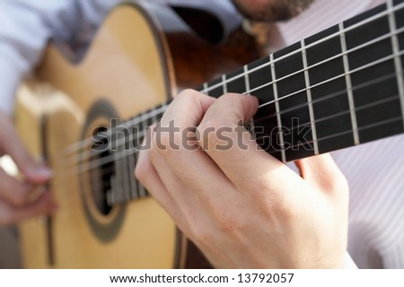 Closeup of man's hands playing classical acoustic guitar DOF focus on hand