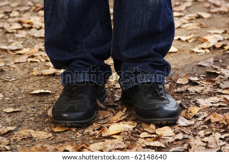 closeup of man's legs in jeans and black boots, outdoor in autumn park