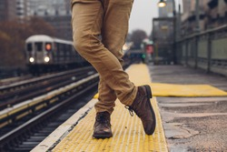 Closeup of  man wearing boots and jeans  in a subway station in New York