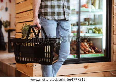 Closeup of man with basket on shopping at grocery shop
