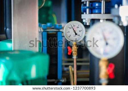 Closeup of manometer, measuring gas pressure. Pipes and valves at industrial plant. Pressure gauge, measuring instrument close up on hot water, oil or gas pipeline #1237700893