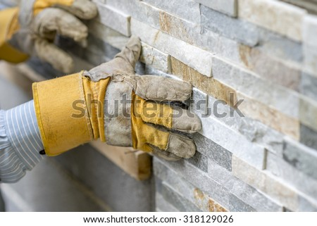 Closeup of manual worker in protection gloves pushing the tile into the cement on the wall while tiling a wall with ornamental tiles l in a DIY, renovation or construction concept. Stock fotó ©