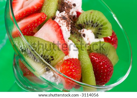 Closeup of martini glass full of fresh kiwi, strawberries and cream with organic yogurt sprinkled by chocolate crumbles over green paper background