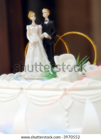 Closeup of marzipan wedding cake with bride and groom figurines on top