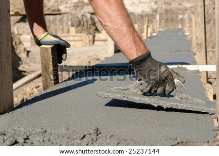 Closeup of mason's hand spreading concrete mix with trowel in foundation shuttering
