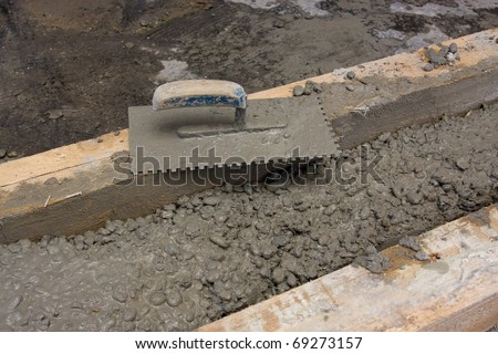 Closeup of mason's trowel on concrete shuttering blocks filled with mortar