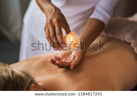 Closeup of masseuse hands pouring wax from a candle on back of mature woman. Beautiful woman at salon spa getting a body oil treatment candle with hot wax. Beauty therapist doing candle massage.