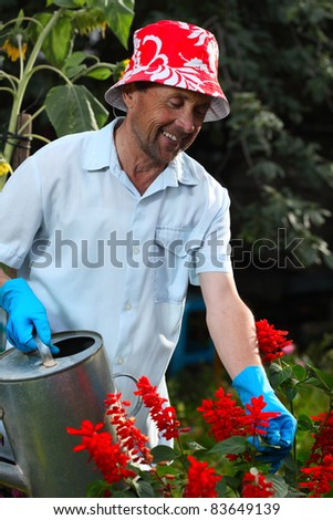 Closeup of mature caucasian smiling man watering her garden with a lot of flowers