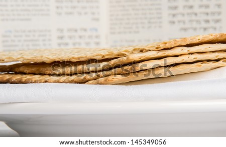 Closeup of Matzah on Plate which is the unleaven bread served at Jewish Passover dinners with Haggadah in background