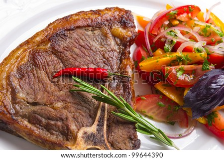 Closeup of meat with vegetables, red pepper and rosemary