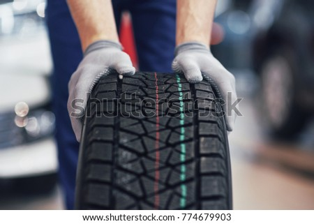 Closeup of mechanic hands pushing a black tire in the workshop. #774679903