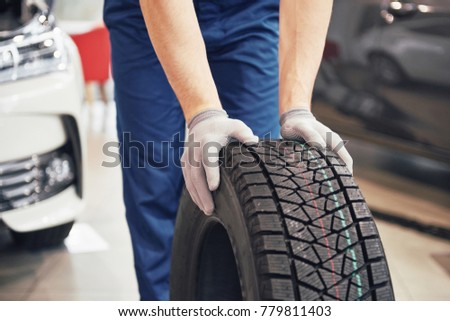 Closeup of mechanic hands pushing a black tire in the workshop. #779811403