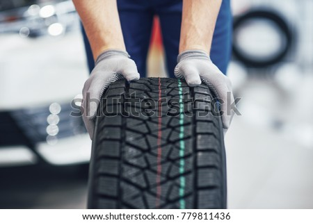 Closeup of mechanic hands pushing a black tire in the workshop. #779811436