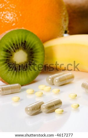 Closeup of medical pills and fruits in background. Shallow DOF. Image suited for health topics about choice between medicine and healthy food