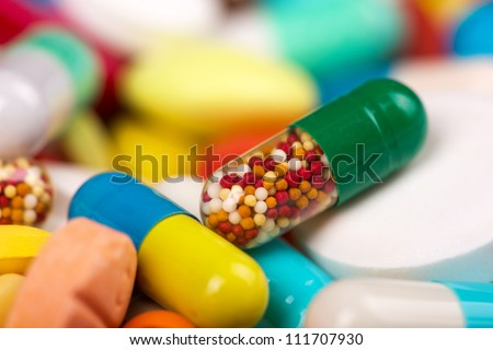 Closeup of medicine capsule against various colorful pills on background
