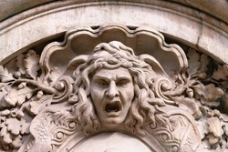 Closeup of Medusa's head carved on the stone facade