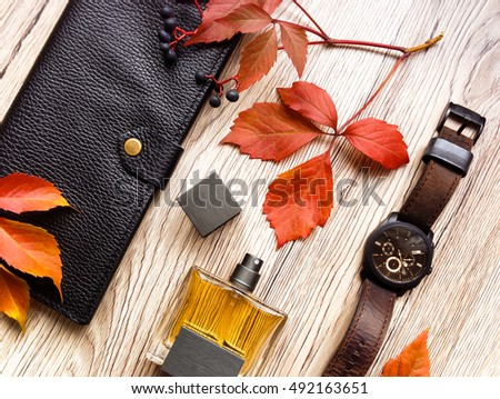 Closeup of men's accessories and essential items on wooden background. Decorated with autumn red leaves. Flat lay, top view, view from above