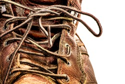 Closeup of Men's Grungy Dirty Beat Up Brown Leather Work Boots with Long Laces Isolated on White Background