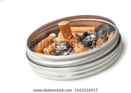Closeup of metallic ashtray full of cigarettes habits on white background