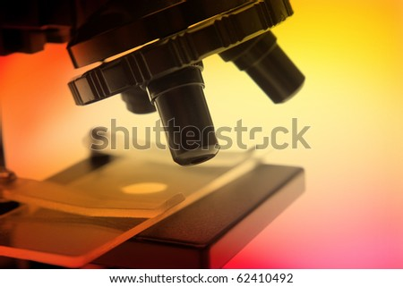 Closeup of microscope on color background