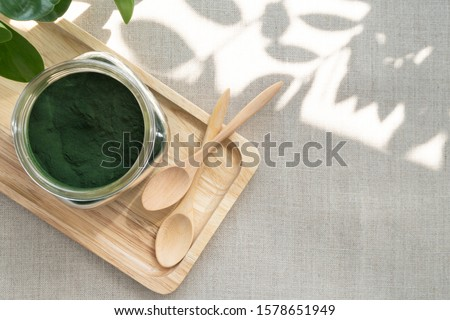Closeup of microscopic blue-green algae - spirulina powder in a glass jar, it is excellent dietary supplement for Vegan, Vegetarian or Plant based diet because it containing multivitamins include B12. Foto stock ©