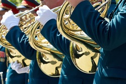 Closeup of military musicians in green uniform and white gloves playing a French horn during a parade in the street.