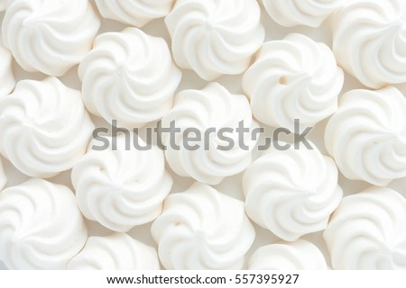 Shutterstock Closeup of mini meringues on white as food background.