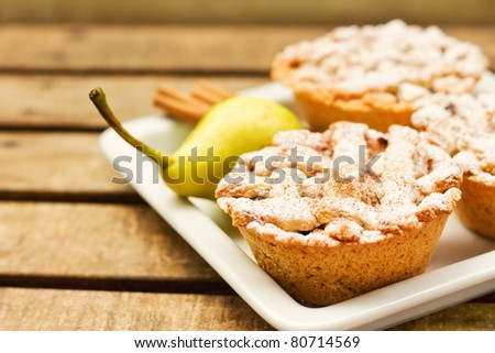 Closeup of mini pies on a plate decorated with cinnamon and a pear  (shallow dof)