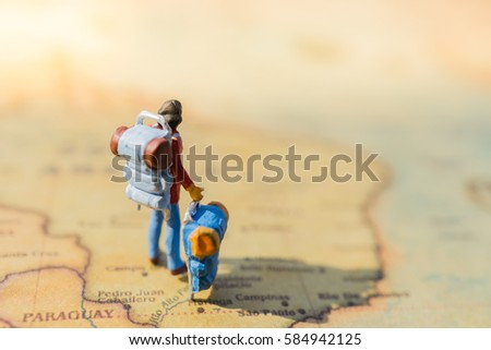 closeup of miniature figurine of young traveler standing on big map next to South America - Brazil/Paraquay