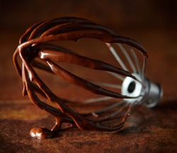 Closeup of mixer whisk with chocolate cake batter sitting on a rust color background