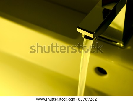 Closeup of modern bathroom tap in yellow - stock photo