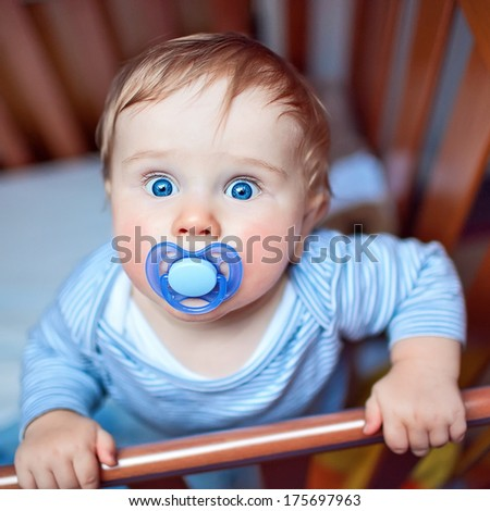 Closeup of 9 months Baby boy with dummy in mouth reaching out of his bed holding the edge with hands and looking up.