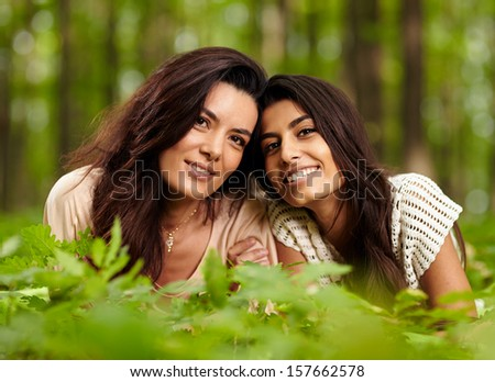 Closeup of mother and daughter laying on blanket at a picnic in a forest
