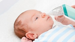 Closeup of mother using electric nasal aspirator to remove mucus from her newborn baby nose. Concept of babies and newborn hygiene and healthcare. Caring parents with little children